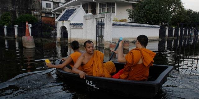 Nov. 6, 2011: Thai Buddhist monks navigate a small boat along flooded streets in Bangkok, Thailand.