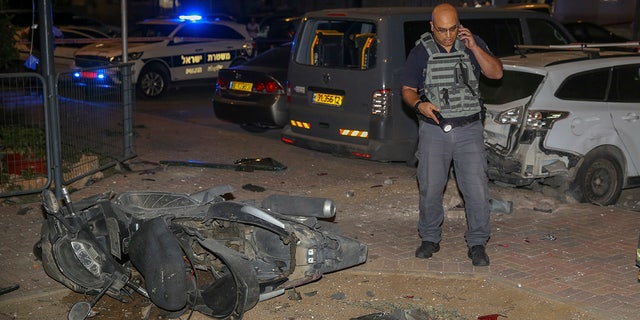 Israeli security stands at the site where a missile from Gaza Strip hit in the town of Sderot, Wednesday, Aug. 7, 2018.