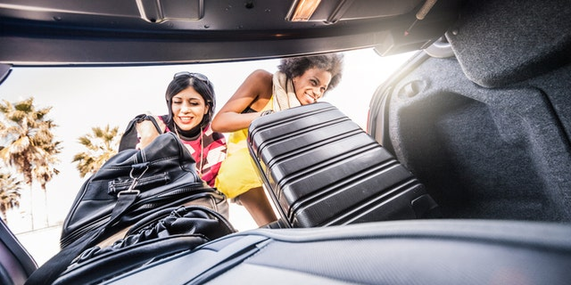 Women friends loading heavy luggages on the car to start a great road trip all over the country. One of is a caucasian young woman, the other one is a mixed race afro