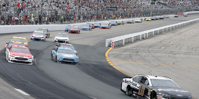 Aric Almirola (10) races ahead of Paul Menard, top left, and Kevin Harvick during the NASCAR Cup Series auto race Sunday, July 22, 2018, at New Hampshire Motor Speedway in Loudon, N.H. (AP Photo/Mary Schwalm)