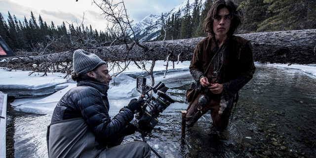 """This photo provided by courtesy of Twentieth Century Fox shows, cinematographer Emmanuel Lubezki , left, and Forrest Goodluck as Hawk on set for the film, """"The Revenant,"""" directed by Alejandro Gonzalez Inarritu. No name is more feverishly celebrated in Hollywood right now than """"Chivo."""" That's the nickname of the famed cinematographer Lubezki, whose acrobatic long-takes and luminous natural images of natural light have made him revered -- and may make him a three-peat Oscar winner for """"Gravity,"""" ''Birdman"""" and now """"The Revenant."""" The Oscars will be presented on Feb. 28, 2016, in Los Angeles. (Kimberley French/Twentieth Century Fox via AP)"""