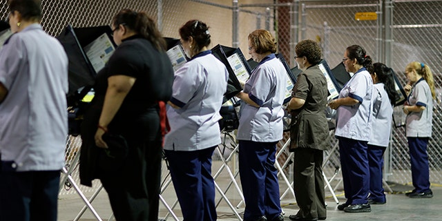 FILE--In this Oct. 26, 2016, file photo, casino workers vote at an early voting site in Las Vegas. Nevada's top election official said Friday the state will provide public voter information requested by a White House commission that is investigating claims of voter fraud in the 2016 election, but will not turn over information such as Social Security numbers of voters and who people voted for. (AP Photo/John Locher, file)