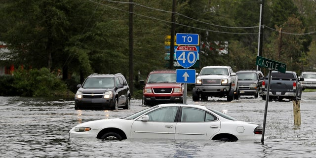 Cars try to navigate a flooded road leading to Interstate 40 in Castle Hayne, North Carolina, after damage from Hurricane Florence cut off access to Wilmington.