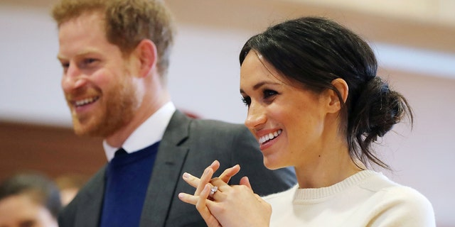 While touring the Titanic Belfast, Markle wore her dark hair pulled back into a low messy bun, only this time it was swept off to one side.