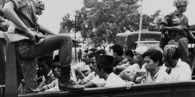 In this Oct. 30, 1965, file photo, members of the Youth Wing of the Indonesian Communist Party (Pemuda Rakjat) are watched by soldiers as they are taken to prison in Jakarta following a crackdown on communists after an abortive coup against President Sukarno's government earlier in the month.