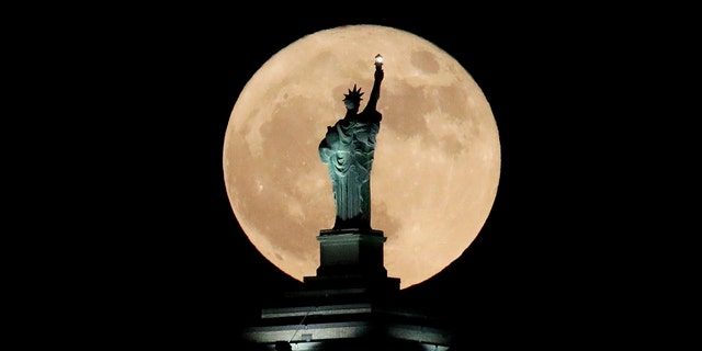 A supermoon rises in front of a replica of the Statue of Liberty sitting atop the Liberty Building in downtown Buffalo, N.Y., Sunday, Dec. 3, 2017.