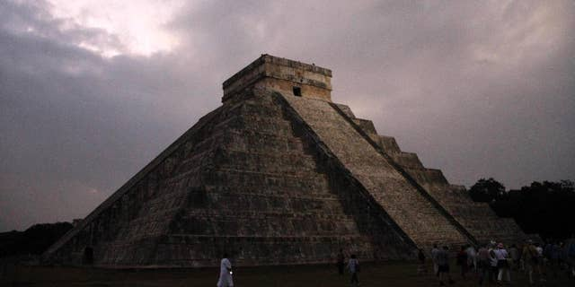 FILE - In this Dec. 21, 2012 file photo, people gather in front of the Kukulkan temple in Chichen Itza, Mexico. Mexican experts said Wednesday, Nov. 16, 2016 they have discovered what may be the original structure at the pyramid of Kukulkan at the Mayan ruins of Chichen Itza. (AP Photo/Israel Leal, File)