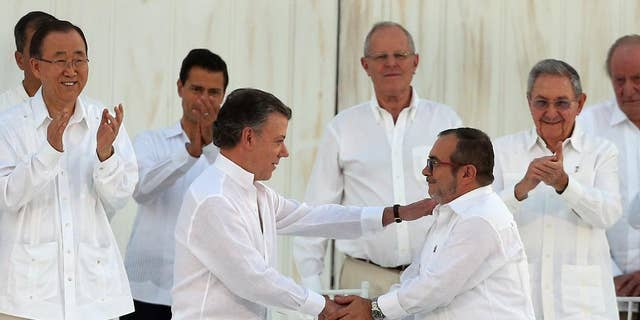 Colombia's President Juan Manuel Santos, front left, and the top commander of the Revolutionary Armed Forces of Colombia (FARC) Rodrigo Londono, known by the alias Timochenko, shake hands after signing the peace agreement between Colombia's government and the FARC to end over 50 years of conflict in Cartagena, Colombia, Monday, Sept. 26, 2016.