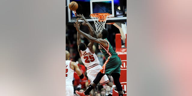 Chicago Bulls' Marquis Teague (25), goes up for a rebound against Milwaukee Bucks' Larry Sanders (8), during the first half of an NBA preseason basketball game in Chicago, Monday, Oct. 21, 2013. (AP Photo/Paul Beaty)
