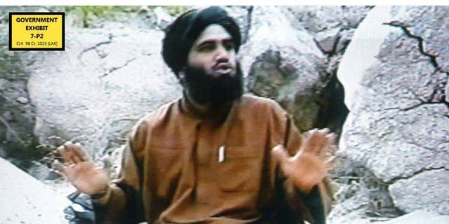 In this undated Photo taken from video and provided by the United States Attorney's Office for the Southern District of New York, defendant Suliman Abu Ghayth, sits on the ground somewhere in Afghanistan. Abu Ghayth, is being tried in New York for plotting to kill Americans by being a motivational speaker at al-Qaida training camps before the Sept. 11 attacks and for serving as a spokesman for the terror group afterward. This photo was among the trial exhibits that the federal prosecutor showed the jury, sometimes repeatedly. (AP Photo/US Attorney's Office for the Southern District of New York)