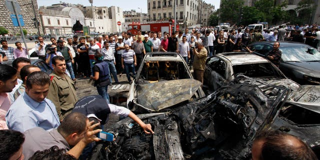 June 28, 2012: Syrians inspect burned cars at the site of a blast in the Syrian capital Damascus.