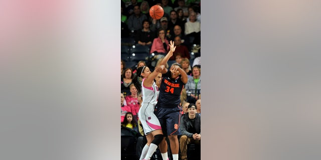 Syracuse center Shakeya Leary, right, passes as Notre Dame forward Natalie Achonwa defends during first-half action of an NCAA college basketball game on Sunday, Feb. 9, 2014, in South Bend, Ind. (AP Photo/Joe Raymond)