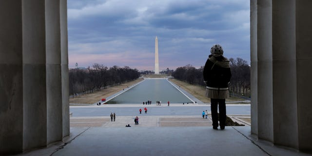This Feb. 28, 2013 photo shows a visitor viewing the National Mall from the Lincoln Memorial looking towards the Washington Monument and the U.S. Capitol in Washington. There are probably more free things to do in the U.S. capital than nearly any other major city in the world. The most popular museums and the zoo are free, thanks to government funding, as well as the picturesque memorials and monuments. With so many free options, the biggest challenge might be narrowing down what to see.  (AP Photo/Alex Brandon)