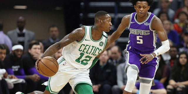 Boston Celtics guard Terry Rozier (12) drives around Sacramento Kings guard De'Aaron Fox (5) during the first half of an NBA basketball game in Sacramento, Calif., Sunday, March 25, 2018.