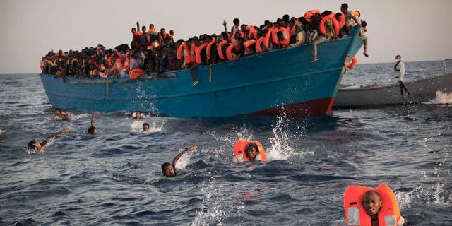 2016 AP YEAR END PHOTOS - Migrants, most from Eritrea, jump into the water from a crowded wooden boat as they are helped by members of an NGO during a rescue operation in the Mediterranean sea, about 13 miles north of Sabratha, Libya, on Aug. 29, 2016. Thousands were rescued from more than 20 boats by members of Proactiva Open Arms before being transferred to the Italian cost guard and other NGO vessels operating in the area. (AP Photo/Emilio Morenatti, File)