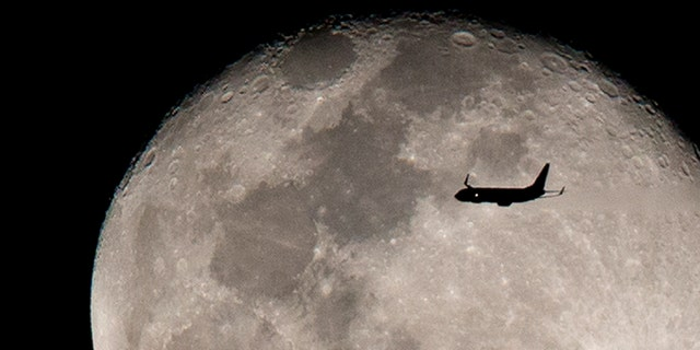 An airplane flies against the backdrop of the rising moon after taking off from Miami International airport, Sunday, Feb. 12, 2017, above Surfside, Fla. (AP Photo/Wilfredo Lee)