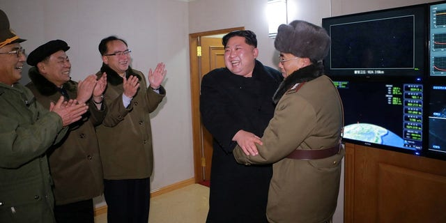 Kim Jong Un celebrates with his rocket scientists after the successful missile launch.