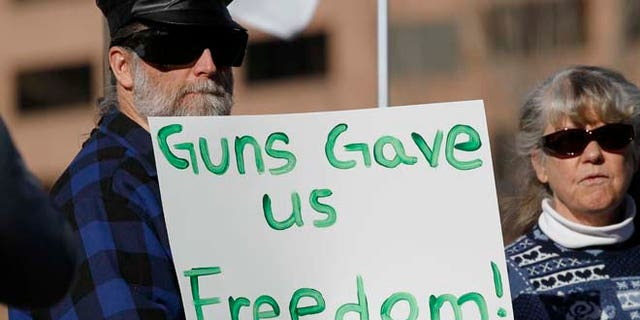 Jan. 9, 2013: Daniel White of Estes Park, Colo., waves a placard at a pro-gun rally as the Colorado Legislature opened its general session across the street in the State Capitol in Denver.
