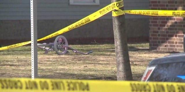 A pink bike is seen on the lawn of the home where a mother and her three children were found dead May 3.