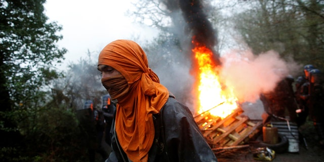 A protester walks past burning debris as French gendarmes continue an evacuation operation.