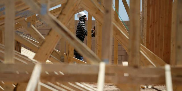 In this April 13, 2015, photo, a worker helps to frame a new home at a housing tract in Las Vegas. The Commerce Department reports on U.S. construction spending in March on Friday, May 1, 2015. (AP Photo/John Locher)