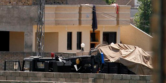 Vehicles are parked inside the compound of a house where it is believed Usama bin Laden lived in Abbottabad, Pakistan, May 2.