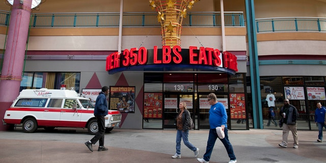 Feb. 15, 2012: Pedestrians pass by the Heart Attack Grill on Fremont Street in Las Vegas.
