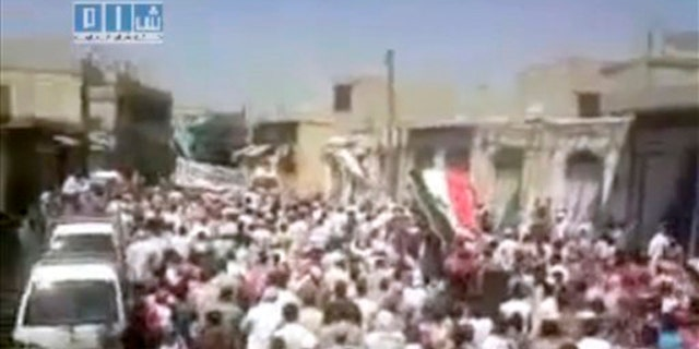In this image posted on the Internet by Shaam News Network, showing what they purport to be a demonstration in the streets of the city of Homs, Syria, on Friday Aug. 5, 2011.