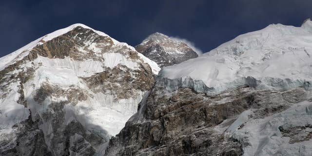 FILE - In this March 7, 2016 file photo, Mount Everest, in middle, altitude 8,848 meters (29,028 feet), is seen on the way to base camp.  High winds have delayed dozens of climbers trying to reach the summit of Mount Everest, a mountaineer official said Wednesday, May 18, 2016. (AP Photo/Tashi Sherpa, File)
