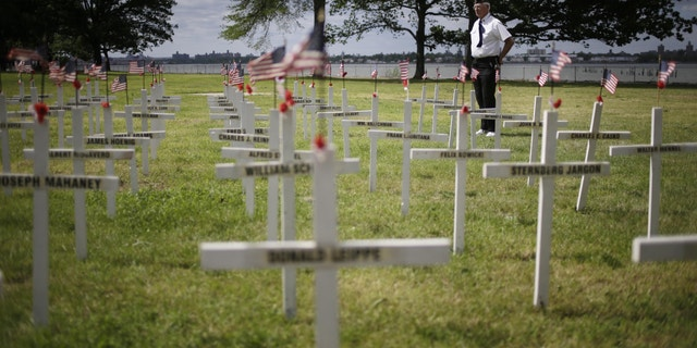 Bob Lewis looks over a field of crosses with names while participating in the College Point Memorial Day Parade in New York, Sunday, May 26, 2013. Lewis made the crosses, 137, for all the service members from College Point that were killed from the Civil War to the Vietnam War. (AP Photo/Seth Wenig)