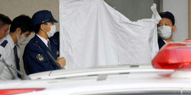 Police officers hide the face of Yoshitane Yamasaki with a sheet while escorting him to a police vehicle.