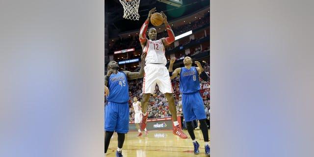 Houston Rockets' Dwight Howard (12) grabs a rebound between Dallas Mavericks Samuel Dalembert (1) and DeJuan Blair (45) in the first half of an NBA basketball game Friday, Nov. 1, 2013, in Houston. (AP Photo/Pat Sullivan)