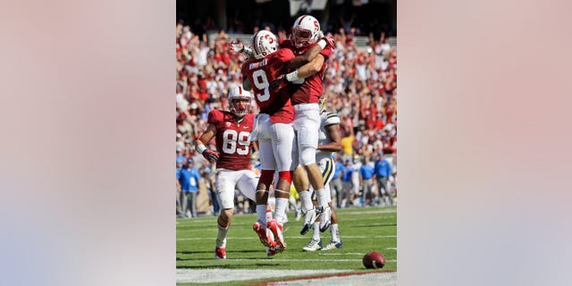 Stanford wide receiver Kodi Whitfield (9) celebrates his touchdown catch with teammate Davis Dudchock, right, during the second half of an NCAA college football game against UCLA  on Saturday, Oct. 19, 2013, in Stanford, Calif. Stanford won 24-10. (AP Photo/Marcio Jose Sanchez)