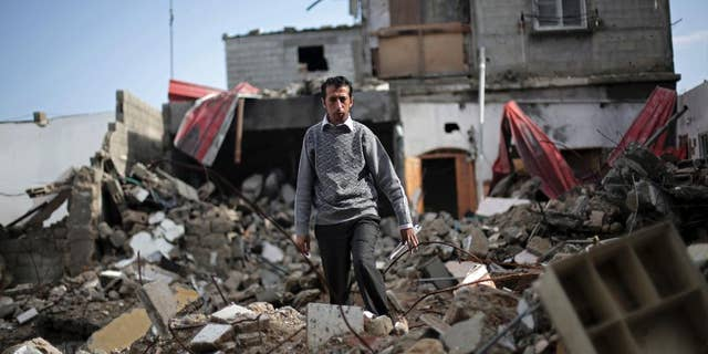 In this Monday, Nov. 17, 2014 photo, Mahmoud Abu Amer, 37, walks amid the ruins of an apartment building where 16 relatives were killed by an Israeli airstrike on July 29, in Khan Younis, Gaza. The building was one of scores targeted by Israel in its war last summer with the Islamic militant Hamas. Israel says it only attacked homes used by militants for military purposes, while Palestinians say warplanes often struck without regard for civilians. (AP Photo/Adel Hana)