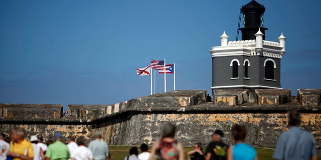 """Tourists walk near the 16th century Spanish fort called El Morro in Old San Juan, Puerto Rico, Jan. 24, 2013. There's an entrance fee to enter the Castillo San Felipe del Morro, but the best way to enjoy this U.S. National Historic Site requires no money at all. The fort that towers over San Juan Bay, known universally as just """"El Morro,"""" is a great place to stroll, especially at sunset. The massive rolling expanse of grass at the foot of the fort has spectacular views in any direction. It's a popular place to picnic and fly a kite, sold by nearby street vendors.(AP Photo/Ricardo Arduengo)"""