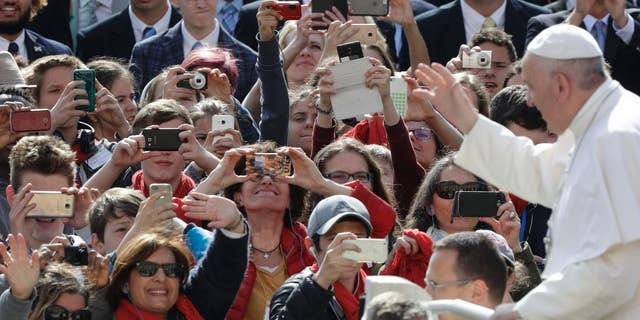 Faithful take snapshots of Pope Francis as he arrives for his weekly general audience in St. Peter square at the Vatican, Wednesday, April 26, 2017. (AP Photo/Andrew Medichini)