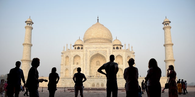Tourists visit India's famed monument of love, the Taj Mahal, in Agra, India, Thursday, March 22, 2018. The 17th century white marble monument is India's biggest tourist draw, with about 3 million visiting every year. [AP Photo/R.S. Iyer)