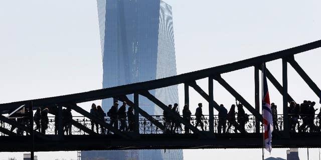 People walk over a bridge near the European Central Bank (background) in Frankfurt, Germany, Monday, May 2, 2016. (AP Photo/Michael Probst)