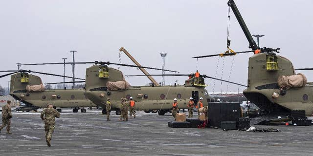 U.S. Technicians prepare helicopters for the transport in Bremerhaven, northern Germany, Sunday Feb. 12, 2017. (Ingo Wagner/dpa via AP)