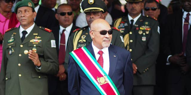 FILE - In this Aug. 12, 2015 file photo, Suriname President Desire Delano Bouterse observes a military parade, after being sworn in for his second term, in Paramaribo, Suriname. A military court in Suriname on Monday, Jan. 30, 2017, ordered the president to resume his long-stalled murder trial in the killing of political opponents under his dictatorship in 1982. (AP Photo/Ertugrul Kilic, File)