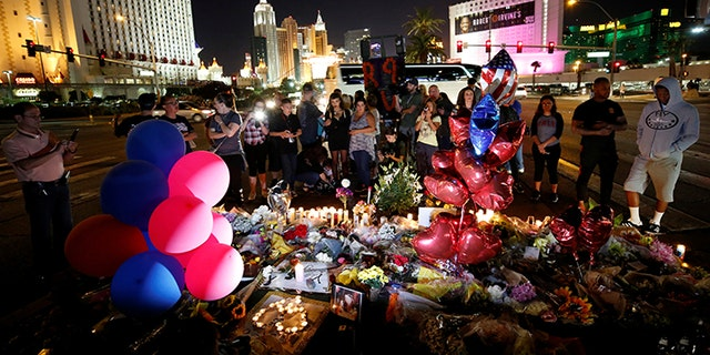 People gather at a makeshift memorial in the middle of Las Vegas Boulevard following the mass shooting in Las Vegas, Nevada, U.S., October 4, 2017.