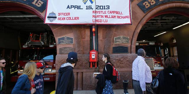 A banner honoring those killed at the 2013 Boston Marathon, and in the immediate aftermath, is draped on the front of Boston Fire Department's Engine 33 and Ladder 15, in Boston, Wednesday, April 15, 2015. Boston marked the second anniversary of the 2013 marathon bombings with a subdued remembrance that included a moment of silence, the pealing of church bells and a call for kindness. (AP Photo/Steven Senne)