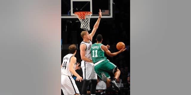Brooklyn Nets forward Mason Plumlee (1) blocks a shot by Boston Celtics guard Evan Turner (11) as Nets forward Bojan Bogdanovic (44) defends from behind  during the first half of a preseason NBA basketball game on Sunday, Oct. 19, 2014 at Barclays Center in New York. (AP Photo/Kathy Kmonicek)