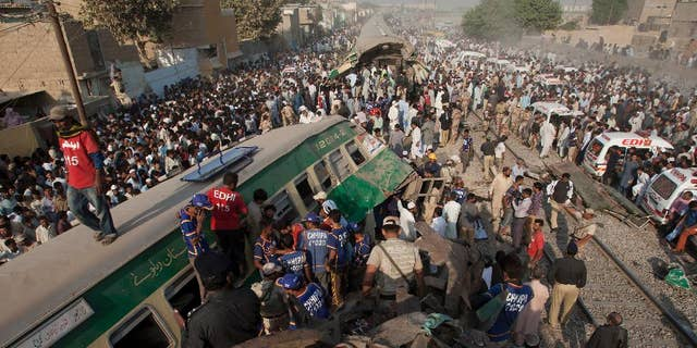 People look for victims in the wreckage of the trains in Karachi, Pakistan, Thursday, Nov. 3, 2016.   Pakistani officials say a train crash has killed dozens of people in the southern port city.  (AP Photo/Shakil Adil)