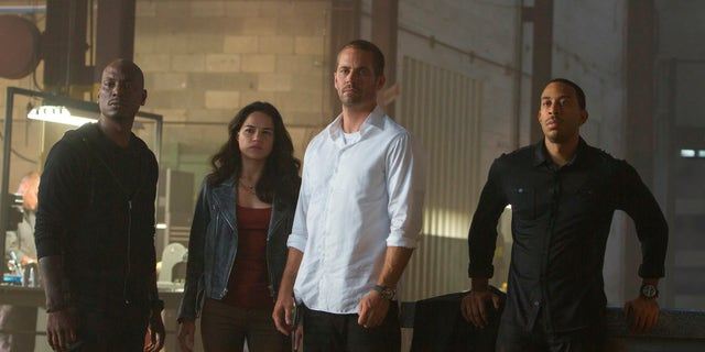 """This photo provided by Universal Pictures shows, from left, Tyrese Gibson as Roman, Michelle Rodriguez as Letty, Paul Walker as Brian, and Chris Ludacris as Tej, in a scene from """"Furious 7.""""  (AP Photo/Universal Pictures, Scott Garfield)"""