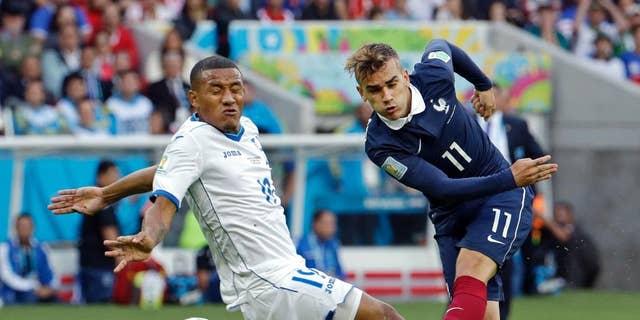 France's Antoine Griezmann drills the ball past Honduras' Luis Garrido during the group E World Cup soccer match between France and Honduras at the Estadio Beira-Rio in Porto Alegre, Brazil, Sunday, June 15, 2014.  (AP Photo/Fernando Vergara)