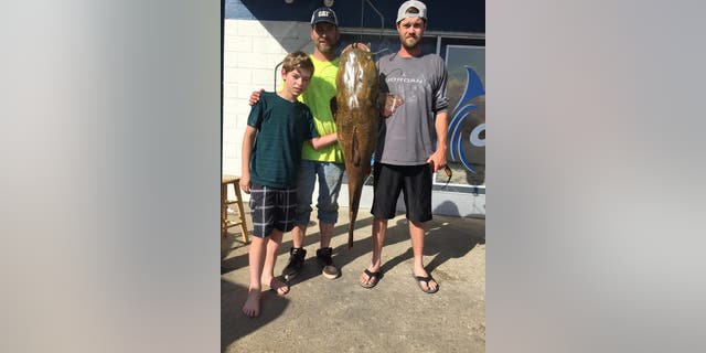 Virginia resident Jeffrey Dill and his family pose with the 68-pound flathead catfish he caught in Lake Smith.