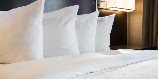 Neatly made hotel bed with 4 pillows.