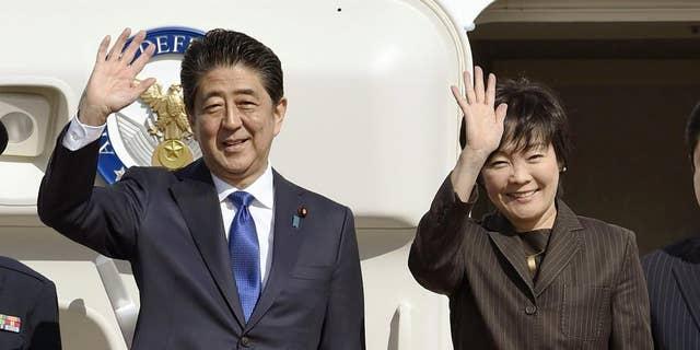 Japanese Prime Minister Shinzo Abe and his wife Akie wave prior to their departure to New York, at Haneda airport in Tokyo Thursday, Nov. 17, 2016. Abe plans to meet with President-elect Donald Trump on Thursday in New York. (Takuto Kaneko/Kyodo News via AP)