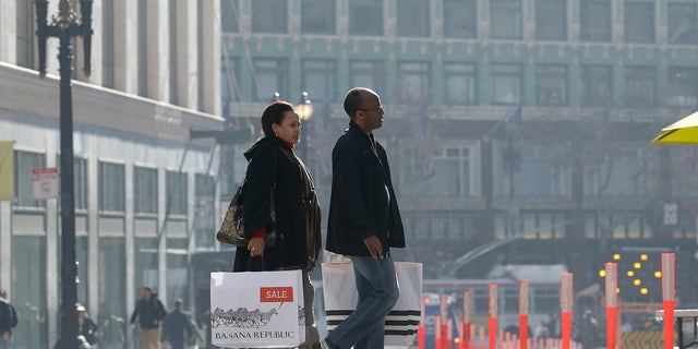 FILE - In this Tuesday, Dec. 24, 2013, file photo, a man and woman carry shopping bags as they cross the street in San Francisco. The Commerce Department reports how much consumers spent and earned in December. on Friday, Jan. 31, 2014. (AP Photo/Jeff Chiu)